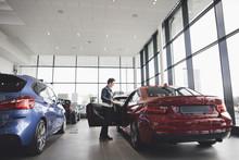 Senior Woman Looking Inside Car In Showroom