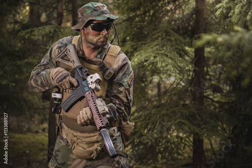 soldier with a rifle in the woods - 113388927
