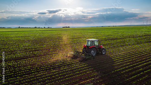 Tractor cultivating field at spring фототапет