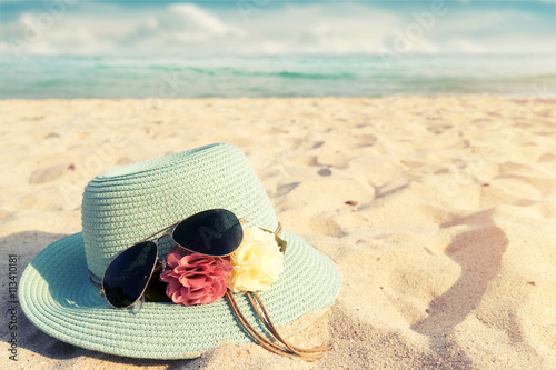 Fotografia  Summer vacation concept with straw hat and sunglasses on sandy tropical beach -