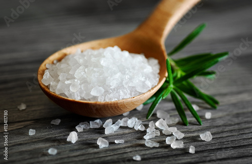 Fototapeta Wooden spoon with salt and rosemary on a dark background. obraz