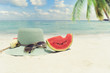 Summer vacation concept straw hat with sunglasses and melon fruit on sandy tropical beach