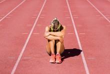 Upset Female Athlete Sitting On Running Track