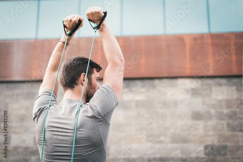 Photo  urban fitness man looking aside while working out  triceps using expander