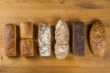 Ciemne i jasne bochenki chleba na drewnianym stole