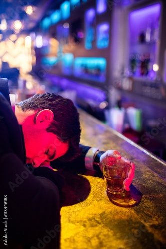 Fotografija  Drunken man sleeping on bar counter