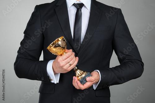 Fotografía  El hombre de negocios que sostiene la taza trofeo de oro