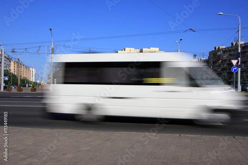 Fotografie, Obraz  Motion white blurred minibus\Motion blurred white minibus on the street in the a