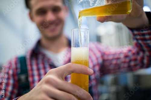 Brewer pouring beer in hydrometer cylinder Canvas Print