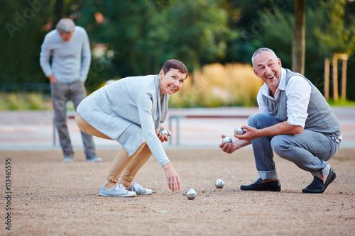 фотография  Senioren beim Boule spielen heben Kugeln auf