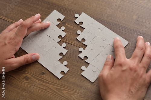 Fotografie, Tablou  Folding puzzle hand parts on a wooden table