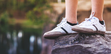 Teenager Legs In White Sneakers On A Rock