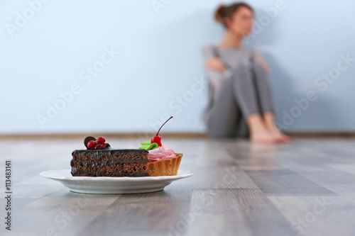 Photo Desperate woman sitting on the floor on grey wall background
