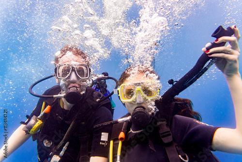 Foto op Plexiglas Duiken Mann und Frau beim Tauchen im tropischen Meer steigen wieder auf nach Tauchgang