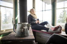 Kettle On Table By Woman Relaxing On Window In Cottage