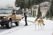 Man And Dog Standing On Snow Covered Street By Car