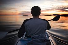 Rear View Of Man Kayaking During Sunset