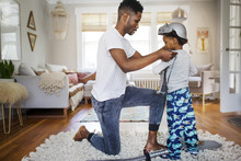 Father Putting Suit Of Armor On Boy At Home