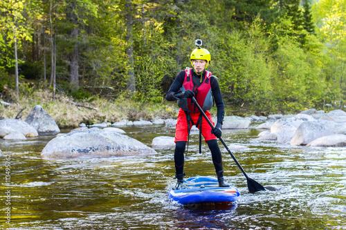 Plakat Mężczyzna supsurfing na bystrzach górskiej rzeki