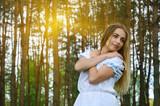 Fototapeta Las - Portrait of beautiful young woman in pine forest