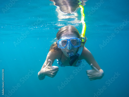 Fotografie, Tablou Underwater shot of the woman moving on the breath hold in the depth