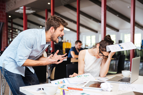 Fotografie, Obraz  Mad crazy businessman arguing with sad stressed businesswoman in office