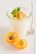 Ein Glas frisch gekochter Milchreis mit Aprikosen steht auf einem weißen Tisch.