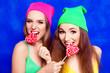 Leinwanddruck Bild - Portrait of attractive happy girls in hats biting lollipops