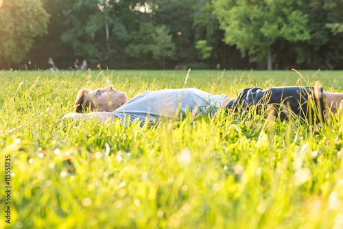 Staande foto Ontspanning A young man lying in the Grass