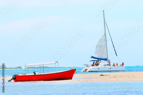 Red motor boat and catamaran on Indian Ocean near Ile Aux Cerfs Island ( Mauritius Island). Blue sea and beach in tropical paradise.