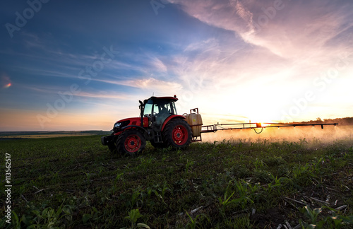 Tractor spraying a field on farm in spring, agriculture плакат