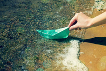 Hand With Paper Boat Near Water