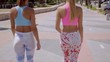 Rear view of two sexy shapely young women in colorful trendy tights or leggings walking along a promenade side by side
