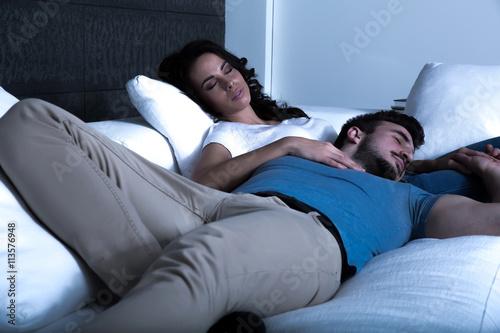 Fototapeta Young couple sleeping on the sofa at night. obraz na płótnie