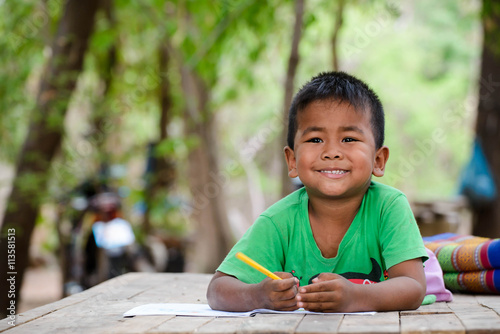 Asian little boy(poor kids) is learning to drawing,painting with color pencil and study at old home.Homeless poor children,smile,lying on dirty wooden table and writing or coloring picture on books.