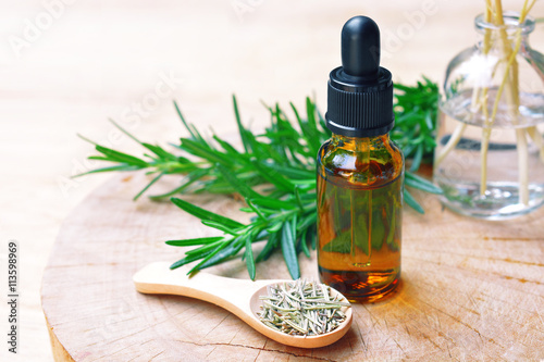 a bottle of rosemary aromatherapy oil extract with fresh and dried rosemary leaf on wooden spoon.