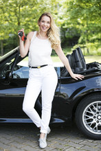 Portrait Of Smiling Blond Woman With Car Keys In Front Of Black Sports Car