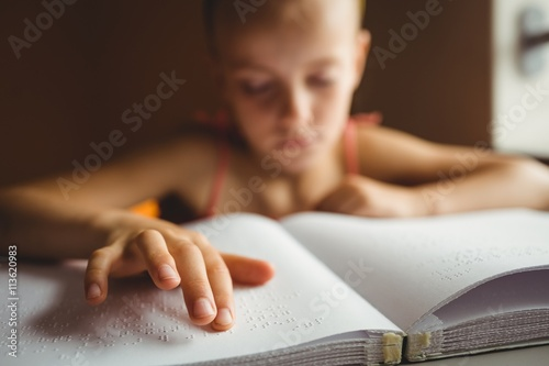 Little girl using his right hand to read braille Canvas Print