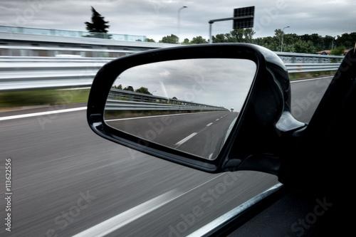Fotografia, Obraz Specchietto retrovisore laterale di una macchina che viaggia in autostrada