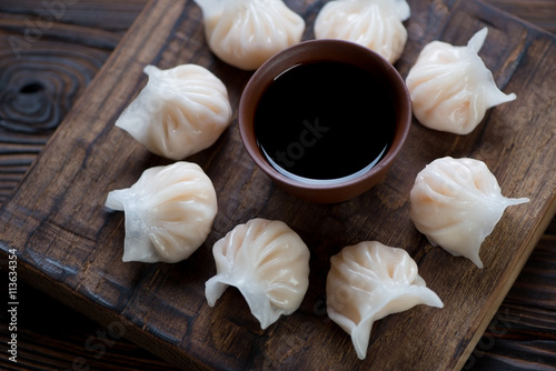 Foto  Rustic wooden serving board with steamed dim sums, closeup
