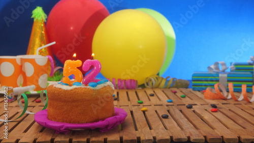 Fotografia  Birthday cake with candles on rustic wooden table with background of colorful balloons, gifts, plastic cups and candies with blue wall in the background