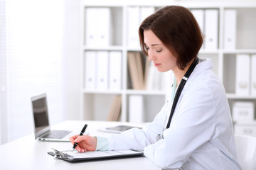 Young brunette female doctor is  sitting at the table and  filling up medical application form.  Health care, insurance and help concept.