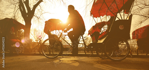 Fotografija Man Riding a Rickshaw China Concept