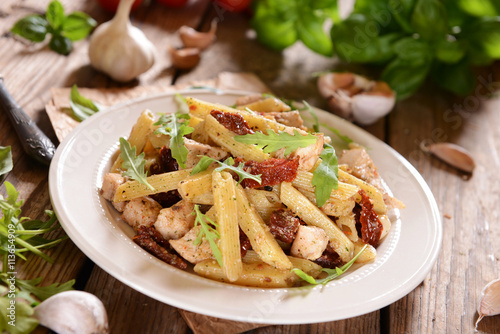 obraz dibond Penne pasta with chicken, dried tomatoes and ruckola