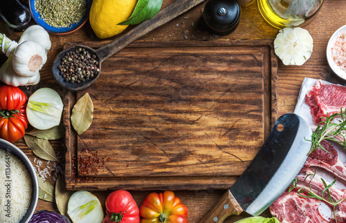 Poster Cuisine Ingredients for cooking healthy meat dinner. Raw uncooked lamb chops with vegetables, rice, herbs and spices over rustic wooden background, dark chopping board in center