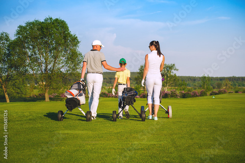 Deurstickers Golf Family golfers plaing golf at sunny day, back view
