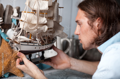 Photo  young man looks at model of sailing ship in vintage interior