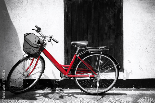 Deurstickers Fiets Black and white photo of red bicycle - vintage film grain filter effect styles