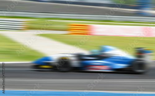Zdjęcie XXL wyścigi samochodowe w drodze z rozmyciem w ruchu i radialnym bluem