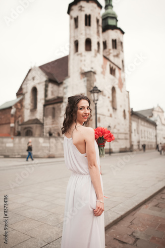 Beautiful young bride with bridal bouquet on the background church Fototapete